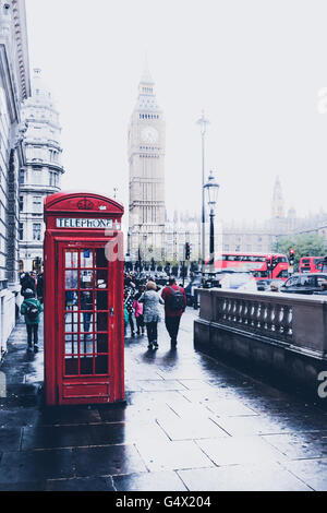 Iconic red telephone booth in front of Big Ben in London, England - Stock Photo
