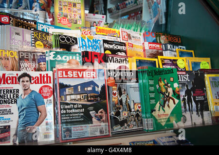 AMSTERDAM,HOLLAND - FEBRUARY 23, 2014: different colored magazines displayed in a kiosk - Stock Photo