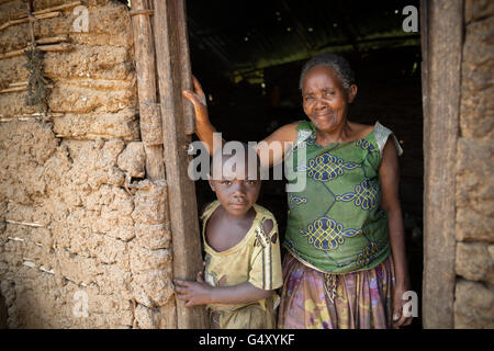 A mother and child stand together in the doorway of their home in rural Kasese District, Uganda. - Stock Photo