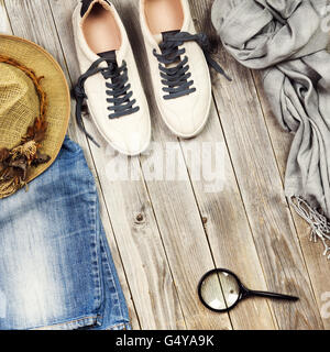 Set of travel items including shoes, scarf, jeans, magnifying glass and straw hat. Different travel objects and passenger luggag