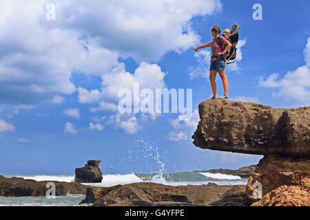 Nature walk on sea beach. Happy mother high rock cliff hold little traveller in carrying backpack. Baby ride on - Stock Photo