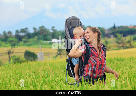 Nature walk in green rice terrace field. Happy mother hold little traveller in carrying backpack. Baby ride on woman - Stock Photo