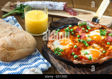 Spanish cuisine. Eggs on vegetables, Andalusian style. Huevos a la flamenca. - Stock Photo