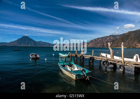 Blue skies over Lago de Atitlan and San Pedro Volcano, Guatemala where boats are moored at the docks on the lakeshore - Stock Photo