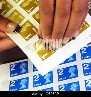 A woman in a Post Office in Overseal, Derbyshire, peels a first-class stamp as the Royal Mail announced that first - Stock Photo