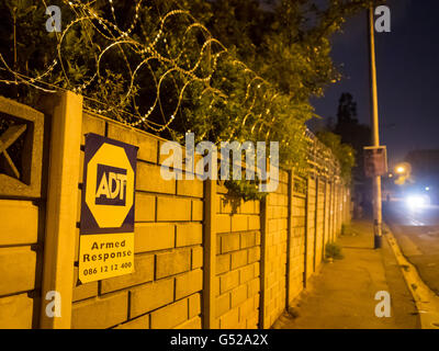 South Africa, Gauteng, Johannesburg, stone wall fence with barbed wire fence, usual protection of the own property - Stock Photo