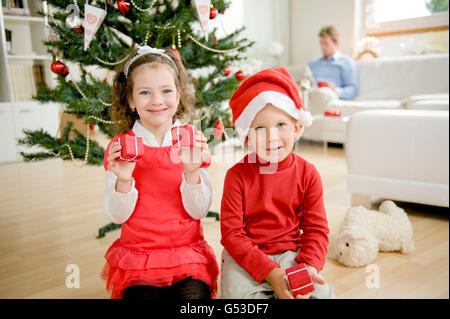 Brother and sister sitting in front of a Christmas tree with Christmas presents - Stock Photo