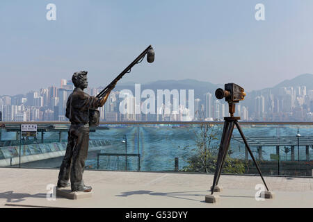 Sound assistant and film camera, bronze sculptures, Avenue of Stars with view of Hong Kong Island, Tsim Sha Tsui, - Stock Photo