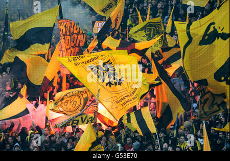 Fans of the football club BVB Borussia Dortmund on the south stand with flags and bengal flares during match Borussia - Stock Photo