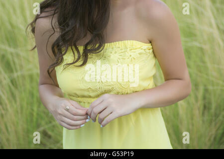 Close up of a woman in yellow dress standing in the meadow - Stock Photo