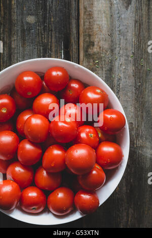 Cherry tomatoes covered with water drops in white bowl on rustic wooden backdrop. Top view, selective focus, toned image