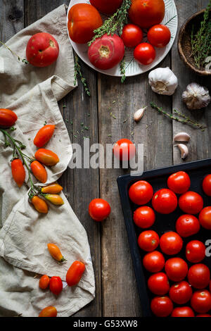 Still life of tomatoes. Fresh heirloom cherry tomatoes, organic tomatoes, garlic and thyme on rustic wooden background - Stock Photo
