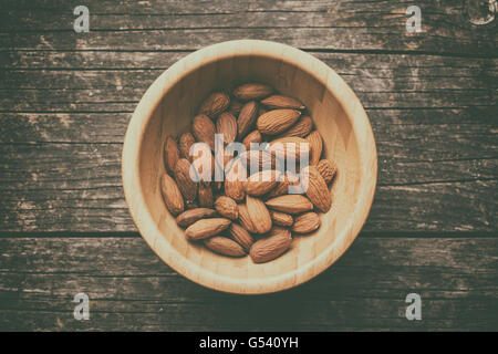 Dried almonds in wooden bowl. Retro filter. - Stock Photo