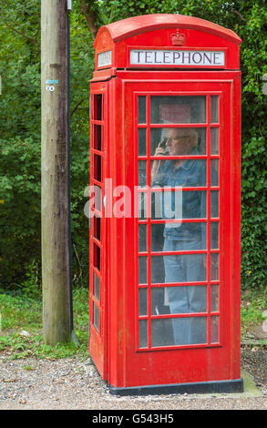 Man using an old style British red telephone box. - Stock Photo