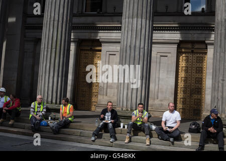 Construction workers sitting on a tea break outside the Gallery of Modern Art, in Glasgow, Scotland, UK. - Stock Photo