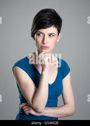 Serious suspicious or worried young short hair woman looking away with hand on her chin - Stock Photo