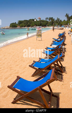 Sri Lanka, Galle Province, Unawatuna beach, line of empty deckchairs in sunshine - Stock Photo