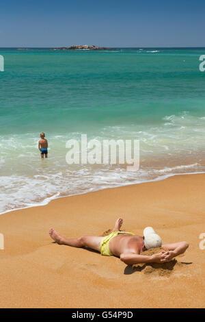 Sri Lanka, Galle Province, Unawatuna beach, sunbather on sand and young boy in shallows - Stock Photo