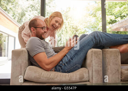 Shot of a happy couple in living room watching something on a digital tablet and laughing. Man lying on sofa with - Stock Photo