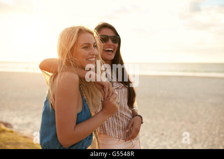 Two beautiful young women strolling on a beach. Female friends walking on the beach and laughing on a summer day, - Stock Photo