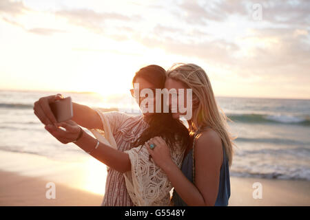 Happy young women enjoying vacation together having fun on the beach and taking selfie photo using smartphone camera. - Stock Photo
