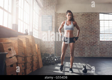 Full length shot of determined fitness woman walking in the crossfit gym. Muscular sportswoman warming up before - Stock Photo