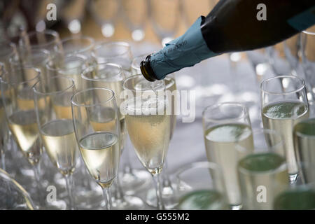 Champagne served in glasses from a bottle during a champagne reception. - Stock Photo