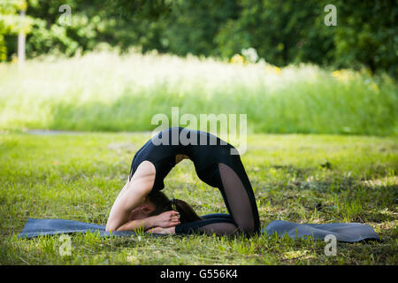 Portrait of beautiful smiling sporty fit blond young woman doing bikram yoga backbend on summer day, Natarajasana, - Stock Photo