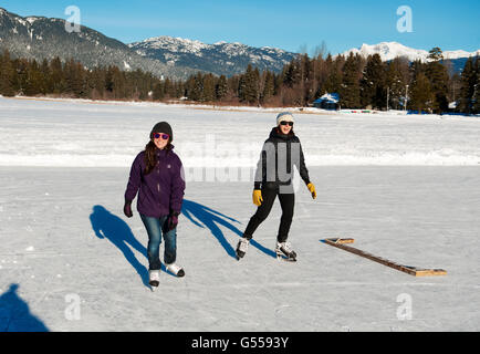 Skaters on frozen Alta Lake on a cold winter day.  Whistler BC, Canada - Stock Photo