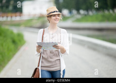 Portrait of casual woman traveler searching direction on location map. Young traveling female walking with map while - Stock Photo