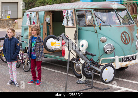 Children posing in front of vintage VW Campervan on display at the Bournemouth Wheels Festival in June - Stock Photo
