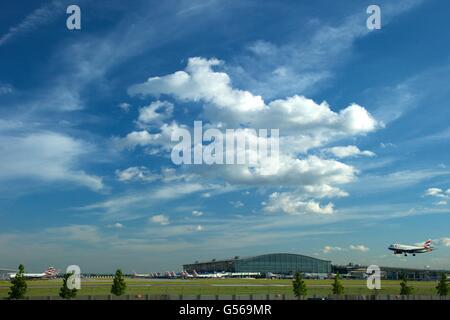 British AIrways flight landing at Heathrow Airport with Terminal 5 behind, London, England, UK, GB, - Stock Photo