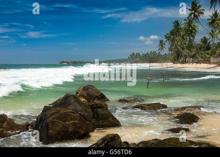 Sri Lanka, Galle Province, Unawatuna, Thalpe, Wijaya, stilt fishermen's poles in water - Stock Photo