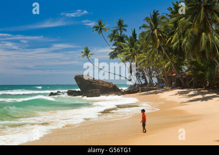 Sri Lanka, Galle Province, Unawatuna, Thalpe, Wijaya young boy alone on tropical beach - Stock Photo