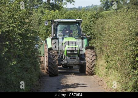 Deutz Fahr tractor driving along narrow country lane, Cumbria, England, September - Stock Photo