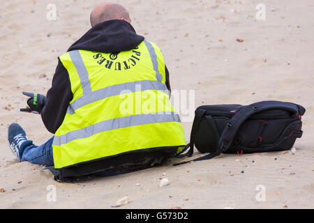 Photographer sitting on beach wearing hi vis vest at Bournemouth Wheels Festival in June - Stock Photo