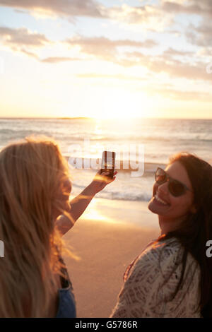 Girls taking a photo of the sunset with mobile phone. Two young women with mobile phone taking pictures of a sunset - Stock Photo
