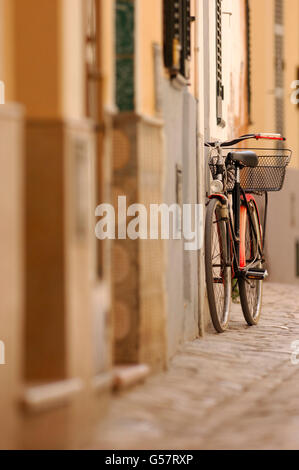 Old Bike with red mudguards and basket leaning up against wall on a cobbled street - Stock Photo