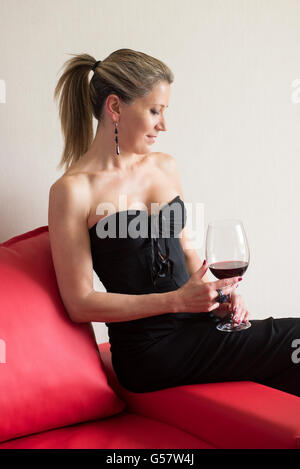 Elegant woman in a black cocktail dress sitting demurely on the arm of a sofa drinking a glass of red wine at a - Stock Photo