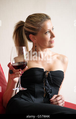 Elegant woman in a black cocktail dress sitting on a red sofa drinking a goblet of red wine - Stock Photo