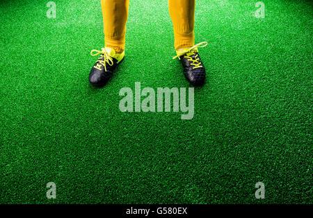 Unrecognizable little football player against green grass, studi - Stock Photo