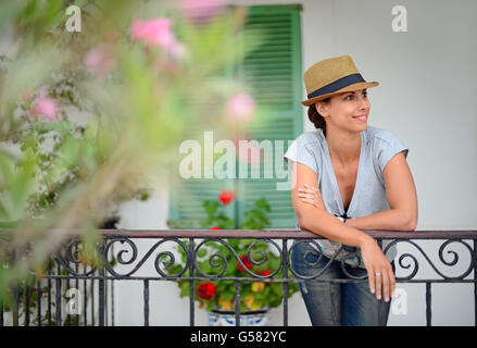 Attractive young woman poses in front of traditional house, Ibiza, Balearic Islands, Spain - Stock Photo