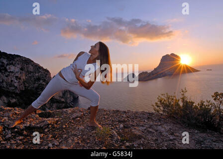 Model Released: Attractive young woman, artist Lena Tancredi, practicing yoga in front of the Mediterranean Sea, - Stock Photo