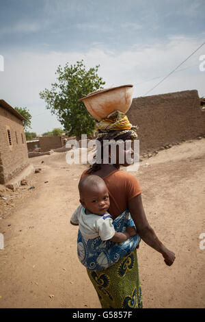 A woman carries a child on her back in Niassan village, Burkina Faso. - Stock Photo