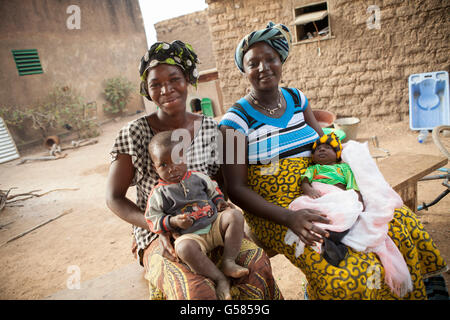 Two women stand together with their children in Niassan Village, Burkina Faso. - Stock Photo