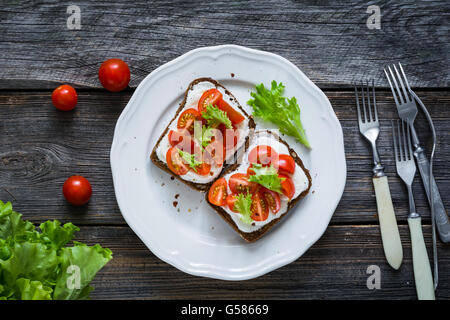 Plate of healthy toasts with cherry tomatoes and ricotta cheese on whole grain rye bread, rustic wooden backdrop, - Stock Photo