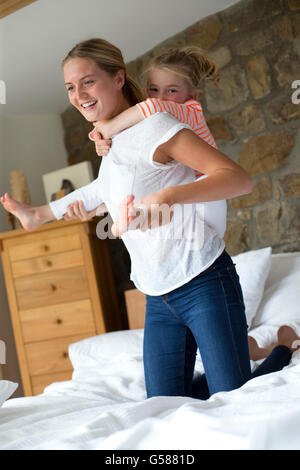 Mother and daughter playing on a bed at home - Stock Photo