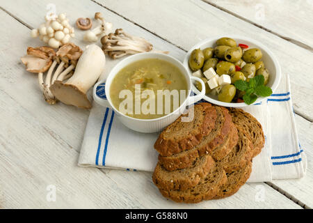 Grunge table board with soup and edible mushrooms - Stock Photo