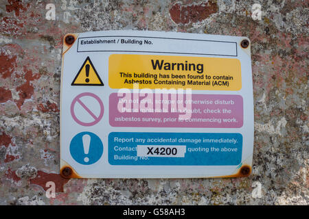 Sign on the exterior wall of a building showing a warning that the building contains asbestos. - Stock Photo