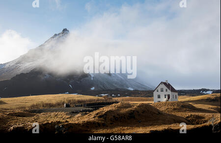 Typical Icelandic landscape with a white small beautiful house under the mountain at Arnarstapi village snaefellsness - Stock Photo